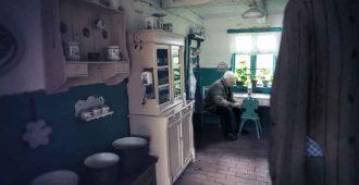на кухне старого дома дед чистит картошку